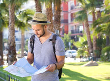 Young man with bag and hat reading map while on vacation Royalty Free Stock Photos