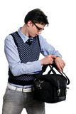 Young man with a bag of looking at the watch Royalty Free Stock Photos