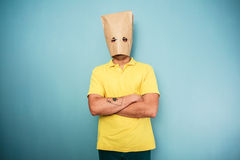Young man with bag over head. Young man with a bag over his head standing with his arms crossed Royalty Free Stock Images