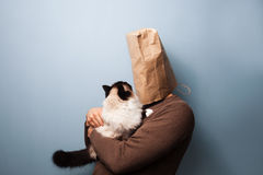 Young man with bag over head holding his cat Stock Images