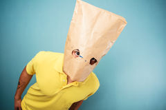 Young man with bag over head looking at camera Royalty Free Stock Images