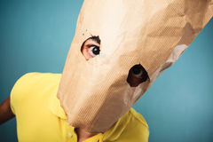 Young man with bag over head looking at camera Royalty Free Stock Photo