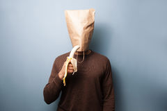 Young man with bag over his head is eating a banana Stock Images
