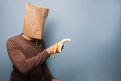 Young man with bag over his head using banana as gun Royalty Free Stock Images