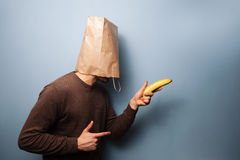 Young man with bag over his head using banana as gun. Young man with a bag over his head using banana as gun Royalty Free Stock Images