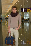 Young man with bag standing in airport hall Stock Image