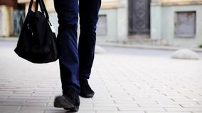Young man with bag walking along city street stock footage
