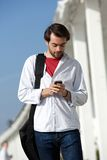 Young man with bag walking and sending text message outdoors Royalty Free Stock Images