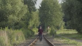 Young man walks on old train tracks. Young Man With A Bag Walking Towards The Camera In Between Railroad Tracks In A Rural Sunny Summer Landscape stock footage