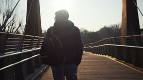 Young man with bag walks along long wooden bridge stock footage