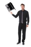 Young man balancing a laptop on his forefinger. Young businessman balancing a laptop on his forefinger, looking at camera royalty free stock image