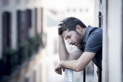 Young man at balcony in depression suffering emotional crisis Royalty Free Stock Images