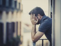 Young man at balcony in depression suffering emotional crisis Royalty Free Stock Image