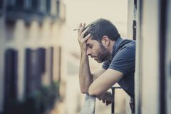 Young man at balcony in depression suffering emotional crisis Stock Image