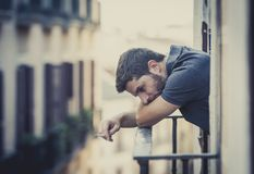 Young man at balcony in depression suffering emotional crisis Royalty Free Stock Photo