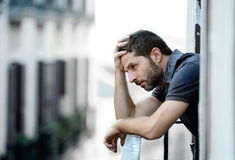 Young man at balcony in depression suffering emotional crisis and grief. Lonely young man outside at house balcony looking depressed, destroyed, sad and royalty free stock images
