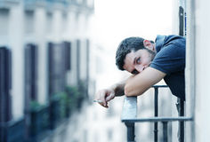 Young man at balcony in depression suffering emotional crisis and grief. Lonely young man smoking outside at house balcony looking depressed, destroyed, sad and royalty free stock image