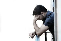 Young man at balcony in depression suffering emotional crisis and grief Stock Image