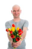 Young man with bald head and bunch of tulips. In front of white background Stock Photo