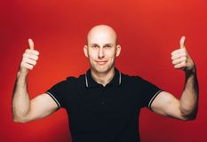 Young man bald portrait on red background thumb up Royalty Free Stock Images