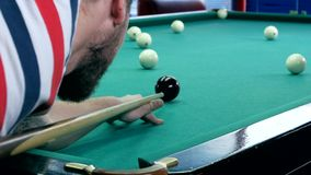 Young man at the ball in a billiard pocket stock footage