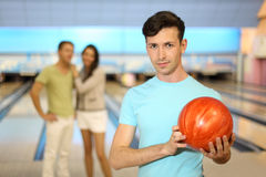 Young man with ball; couple stands behind him Royalty Free Stock Image