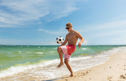 Young man with ball playing soccer on beach Royalty Free Stock Photo