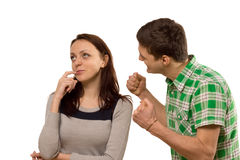 Young man balling his fists in frustration. Young men balling his fists in frustration at his girlfriend as she stands thinking unable to make up her mind or Royalty Free Stock Image