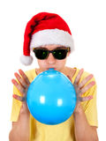 Young Man with Balloon. Young Man in Santa Hat inflate a Blue Balloon Isolated on the White Background Royalty Free Stock Photo