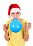 Young Man with Balloon. Young Man in Santa Hat inflate a Blue Balloon Isolated on the White Background Stock Photography
