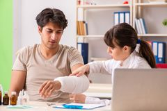 Young man with bandaged arm visiting female doctor traumatologis. T stock image