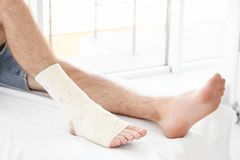 Young man with bandaged leg. In clinic stock photos