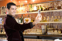 Young man by bar with drink, taking photograph, smiling Royalty Free Stock Image