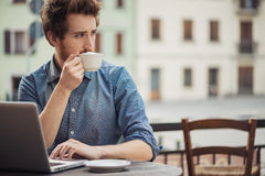 Young man at the bar with a laptop Royalty Free Stock Image