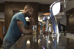 Young man at the bar. Young man standing at the bar looking deep in thought, with a pint in his hand stock photography