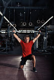 Young man with barbell in gym royalty free stock photos