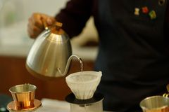 Young man barista pouring coffee royalty free stock photography