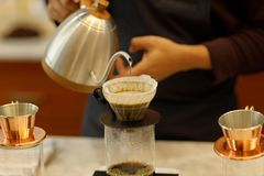 Young man barista pouring coffee royalty free stock photos