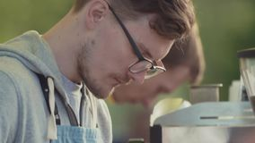 Young man barista puts coffee beans into machine at outside festival stock footage