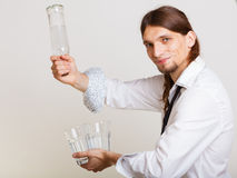 Young man bartender pouring a drink, studio shot Stock Image