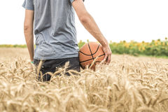 A young man with a basketball on the nature, concept of sport stock photo