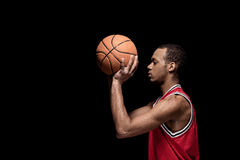Young man basketball player with ball on black Royalty Free Stock Photos