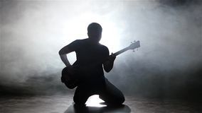 Young man bassist playing guitar on his knees. Slow motion. Young man bassist playing guitar on his knees, man dressed in a dark shirt and jeans, studio is stock footage