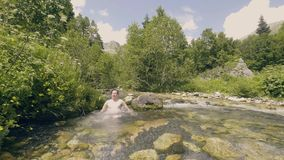 Young man bathing in refreshing water of stony river slow motion stock video footage