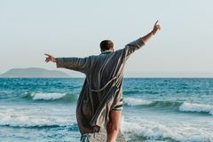 Young man in a bathrobe on the beach royalty free stock photography