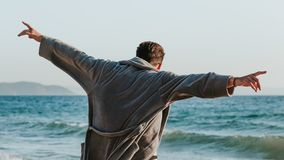 Young man in a bathrobe on the beach stock images