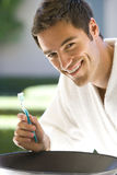 Young man in bathrobe brushing teeth, smiling, portrait Stock Images