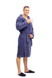 Young man in bathrobe holding a cup of coffee Stock Photography