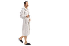 Young man in a bathrobe holding a cup and walking. Full length portrait of a young man in a bathrobe holding a cup and walking isolated on white background stock photo