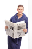Young man in a bathrobe holding a newspaper Royalty Free Stock Photography